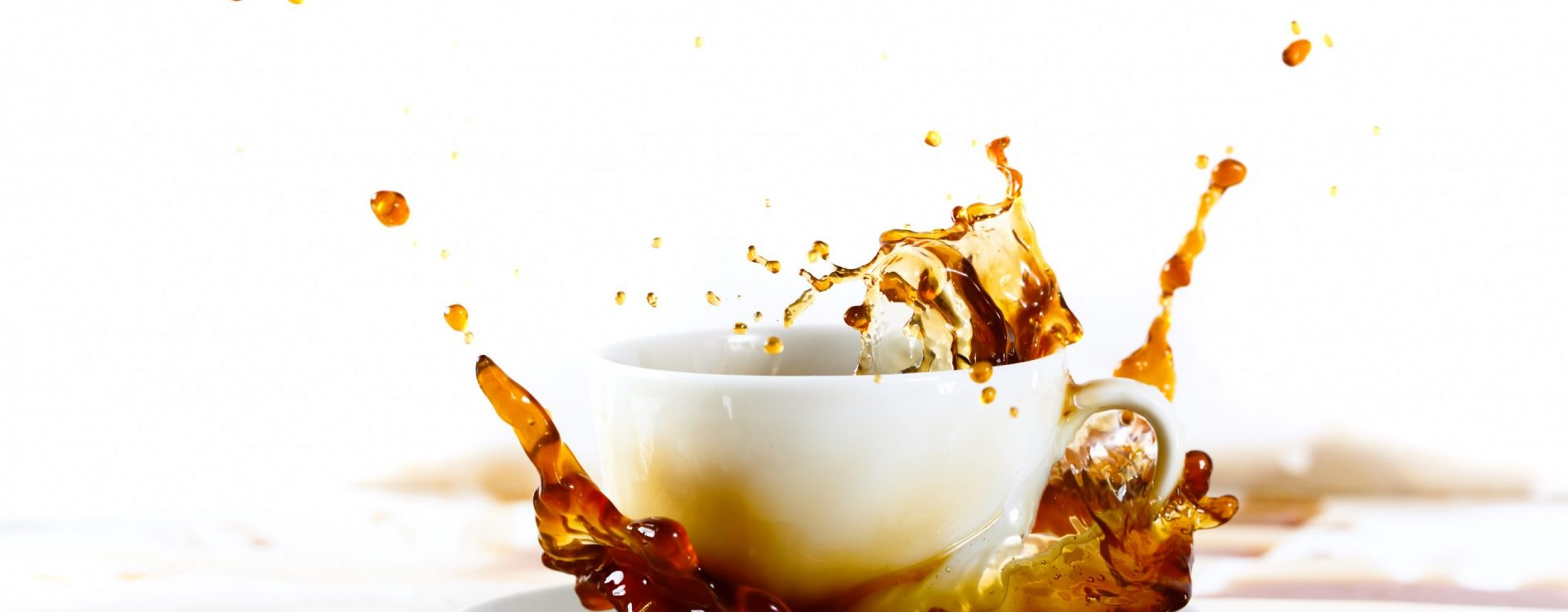 Cup of coffee creating splash. White background, coffee stains. Coffee break, breakfast concept.