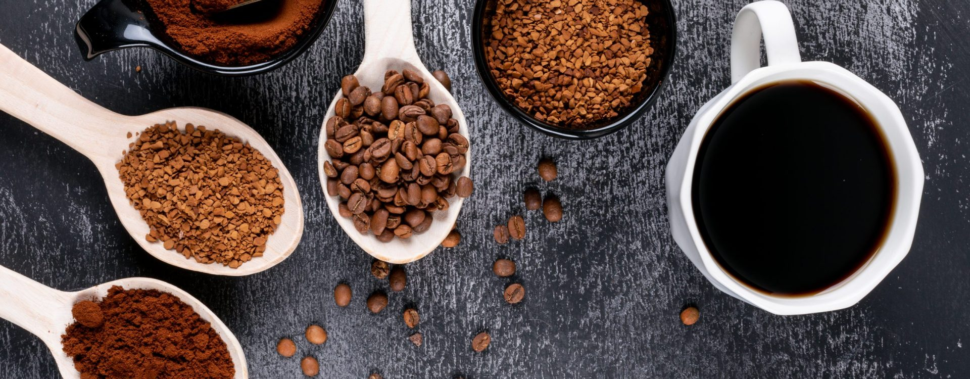 top view instant coffee in wooden spoons and coffee cup on dark background